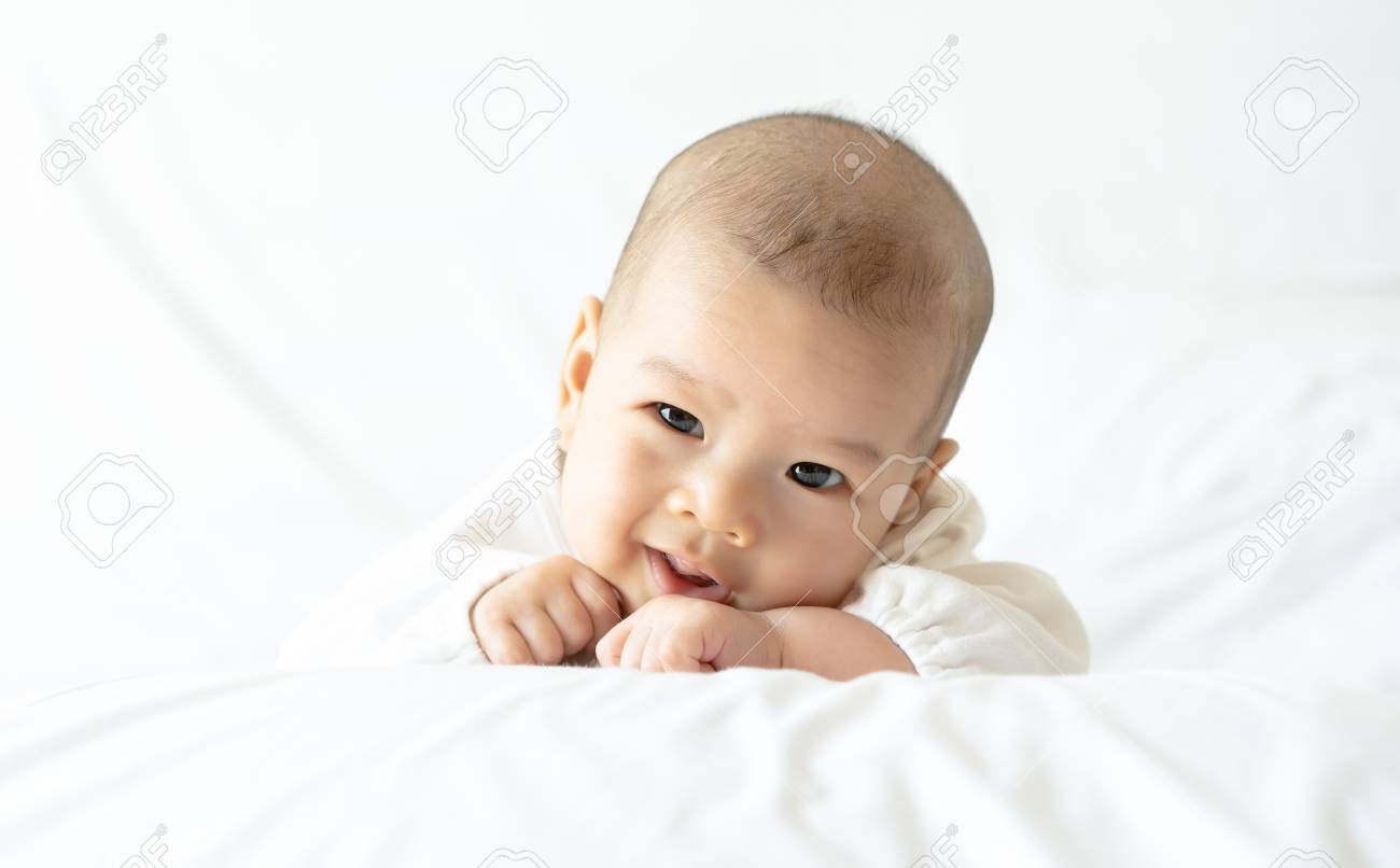 Cute happy little baby smiling in white bed.Newborn child relaxing in bed. Nursery for children.Family, new life, childhood, beginning concept. - 124939099
