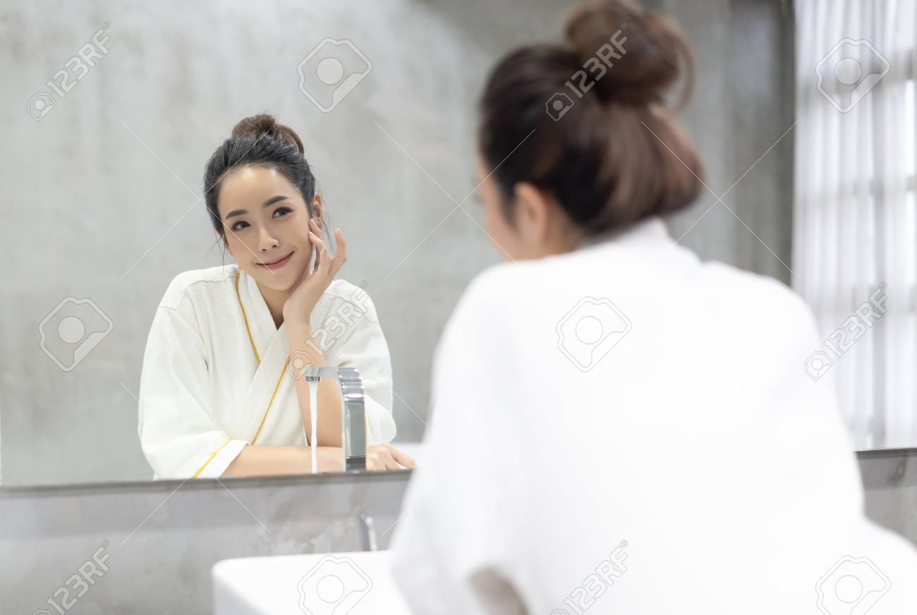 Facial Beauty.Beautiful smiling young Asian woman in bathrobe applying moisturizer cream on her pretty face and looking to mirror at bathroom, touching face with hands . Natural skin care and people Concept. - 124939647