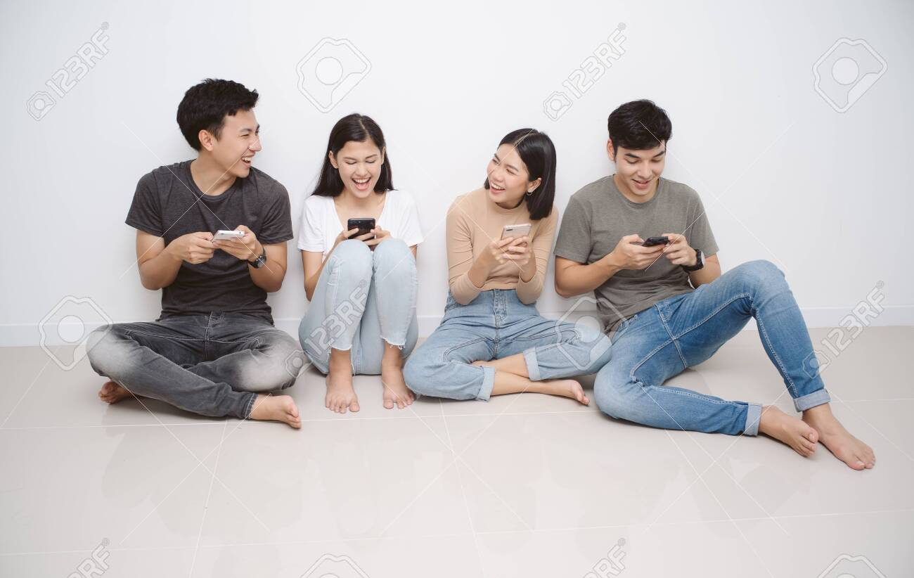 Group of friends sitting on the floor using smart mobile phones. People addiction to new technology trends. Concept of youth, z generation, social network and friendship. - 123523916