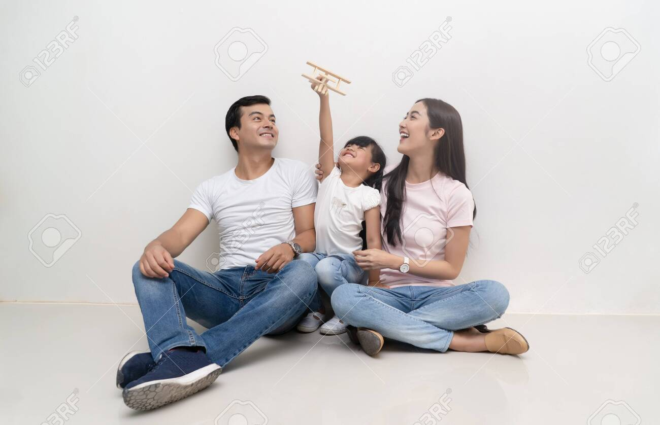 Happy multiethnic family sitting on the floor and playing toy airplane together. Family and childhood concept. - 123523971