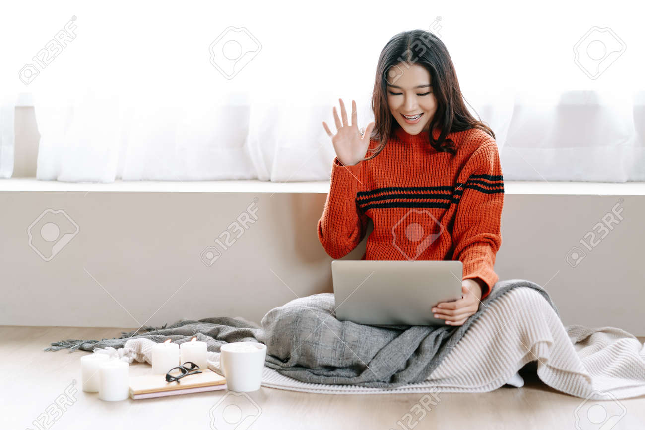 Portrait of young Asian woman smiling friendly using laptop computer have online video call broadcast meet bloggers say hi while sitting on floor at home in winter. Cozy winter decorated with candles. - 162360798