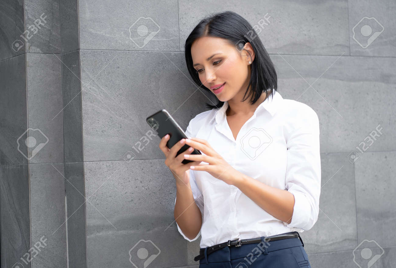 Portrait of young businesswoman using her smartphone, chatting on social media standing outdoor near office. - 173415222
