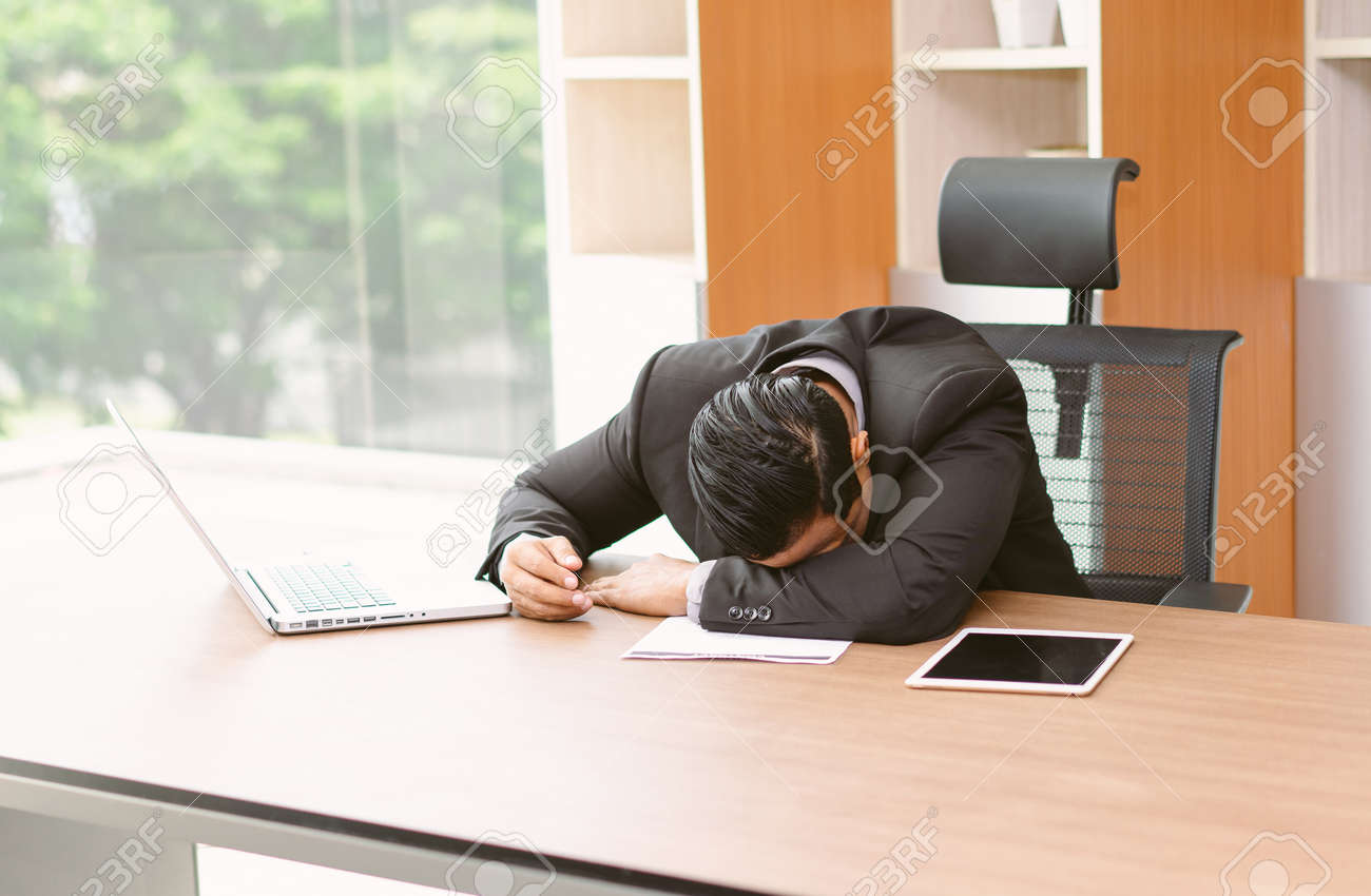 Portrait of tired and sleepy Asian businessman in office desk. He worked and fell asleep on the desk. Stress at work and Lack of motivation concept. - 171622254