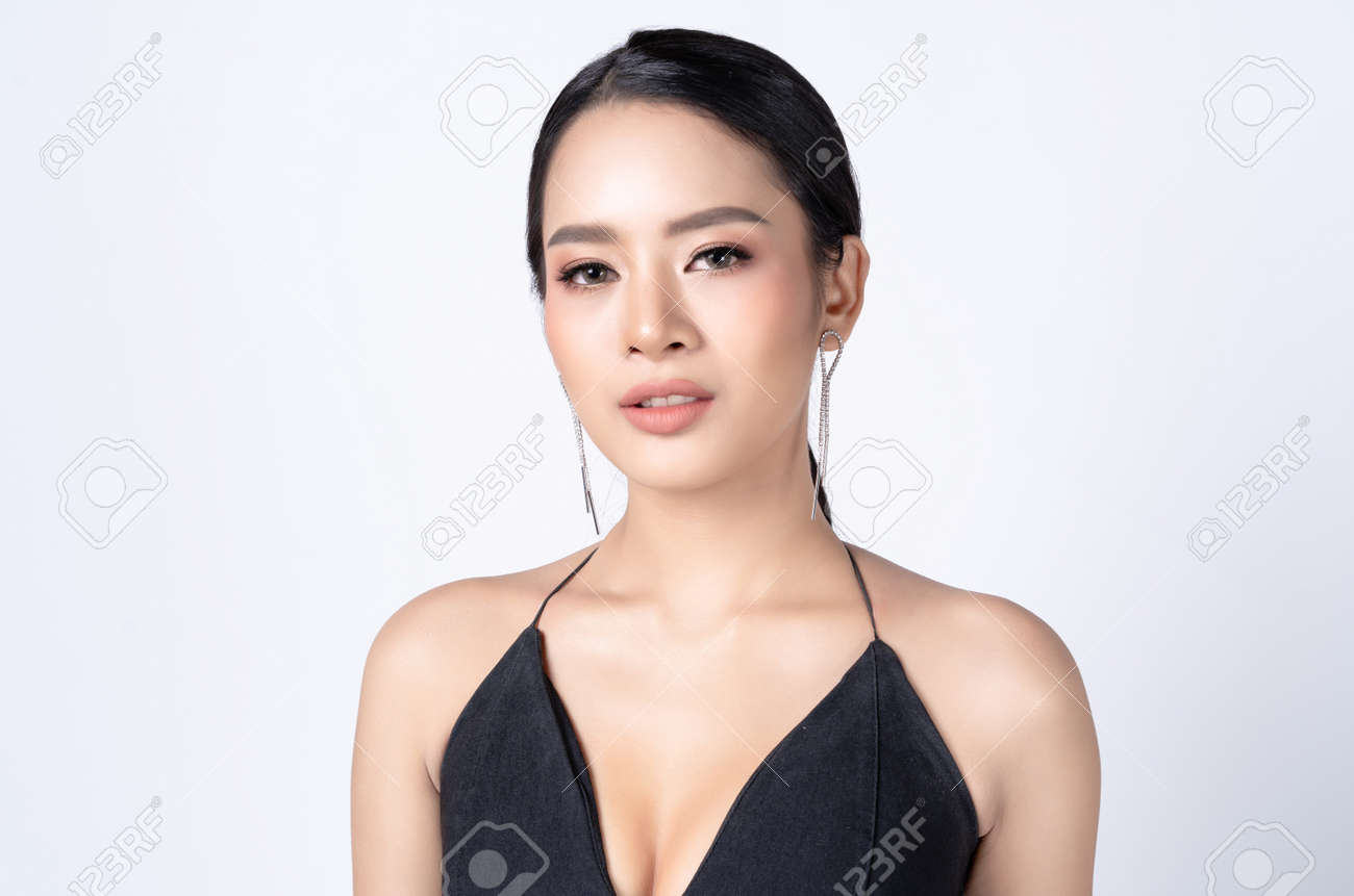 Glamour portrait of beautiful Asian woman in Sexy Black Dress with tassel earrings silver and looking at camera. Fashion shiny highlighter on skin and gloss lips, perfect make-up. - 171622275