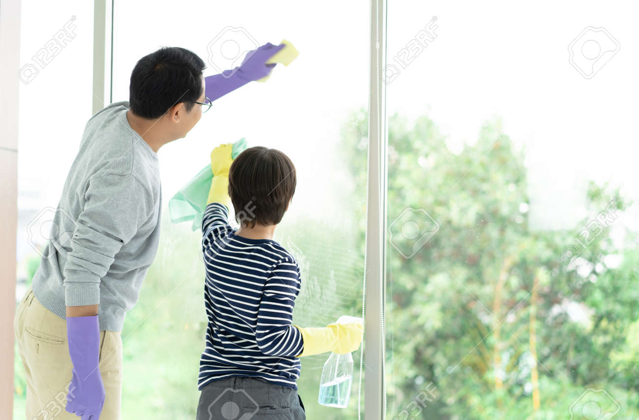Asian Family Cleaning Day. Happy Dad and son cleaning window together on Holidays. Family housework and household concept. - 171625569