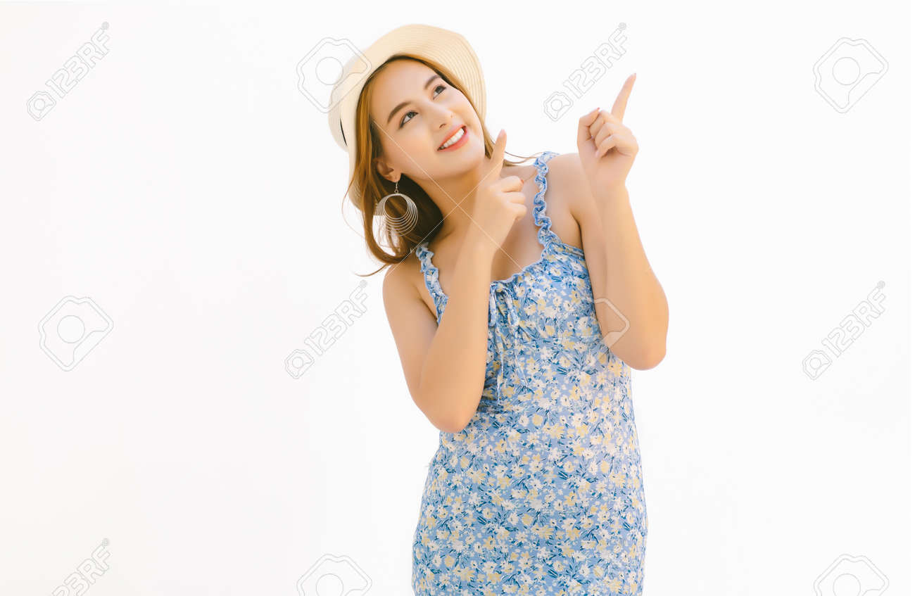 Beautiful young Asian woman dressed in blue floral dress and wearing summer straw hat pointing fingers up with two hands at copy space isolated over white background. - 173415221