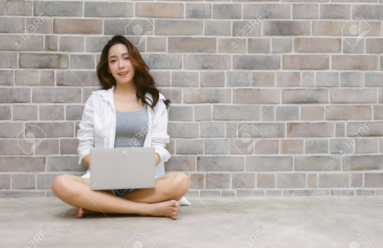 Portrait of happy Korean girl in casual sitting on floor with crossed legs while using laptop computer and looking at camera at copy space on brick wall background. Technology and lifestyle concept. - 172026287