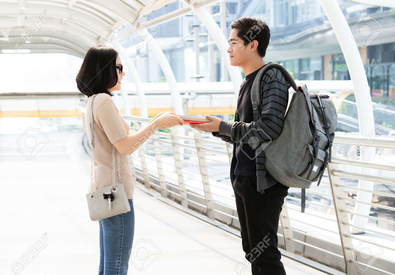 Portrait fo a cheerful young Asian couple exchanging different books on the city. Person borrow textbook, swap of knowledge. Give to read to a boyfriend. - 171987095