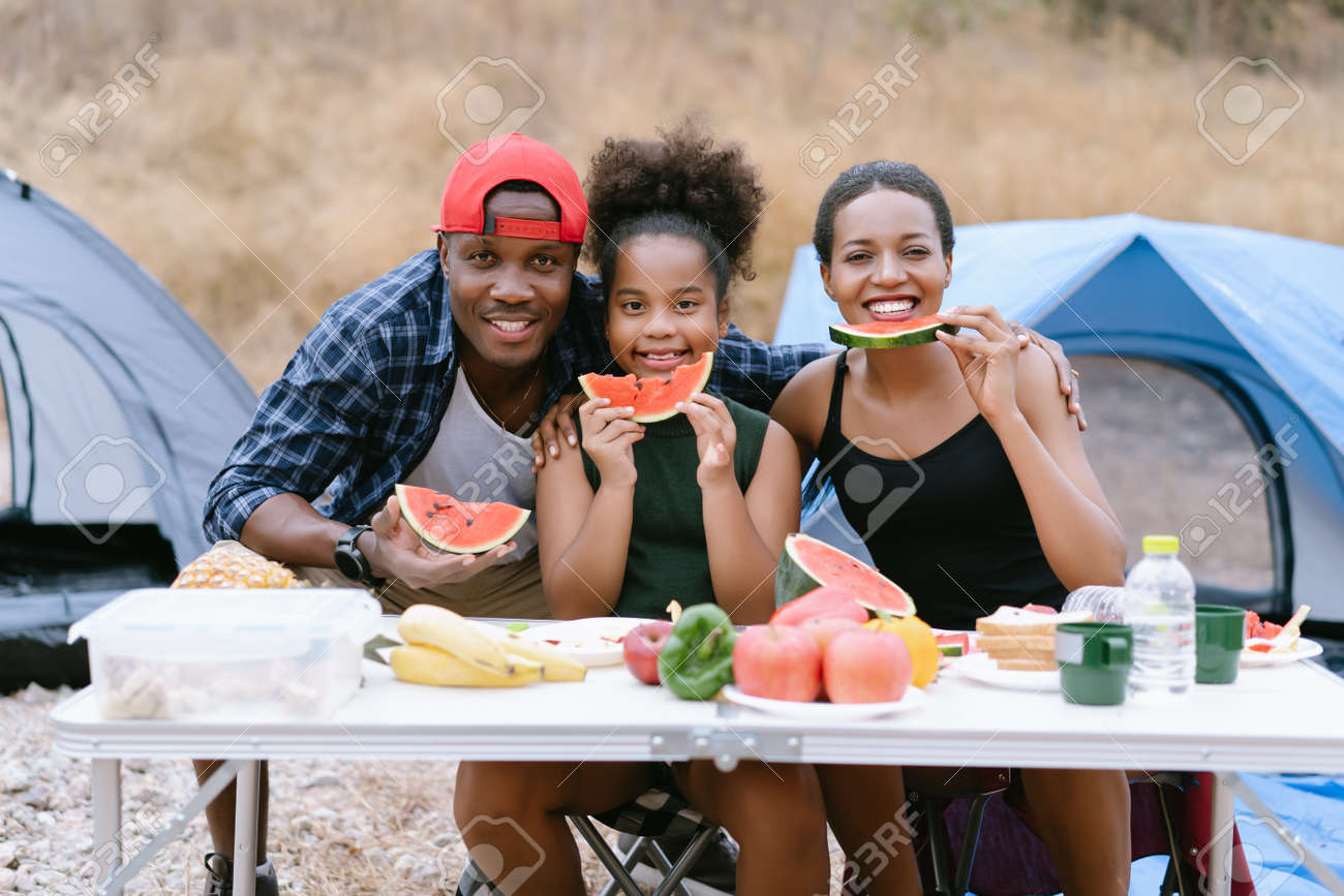 Portrait of african american family having fruit and snack outside the tent at campsite and looking at camera. Holiday Family activity outdoor concept. - 173415225