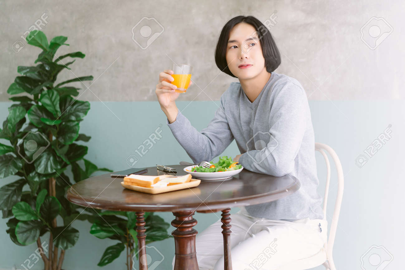 Portrait of young Asian man eating at restaurant table healthy food, drinking orange juice, dining alone and looking away, tourist at restaurant of his hotel. Healthy Lifestyle concept. - 173415229