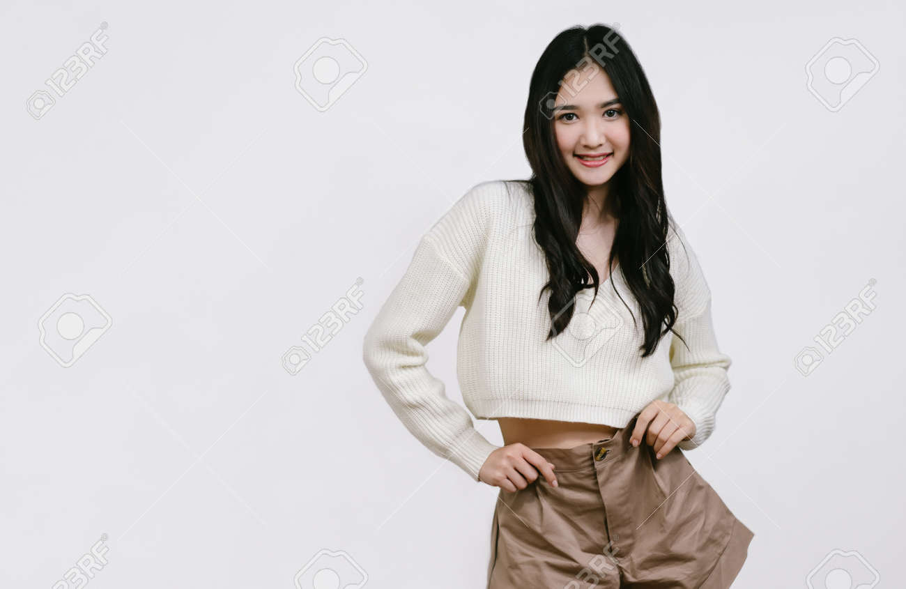 Beautiful young Asian woman in brown shorts and white sweater standing smiling looking camera on isolated over white background with copy space. - 172634607