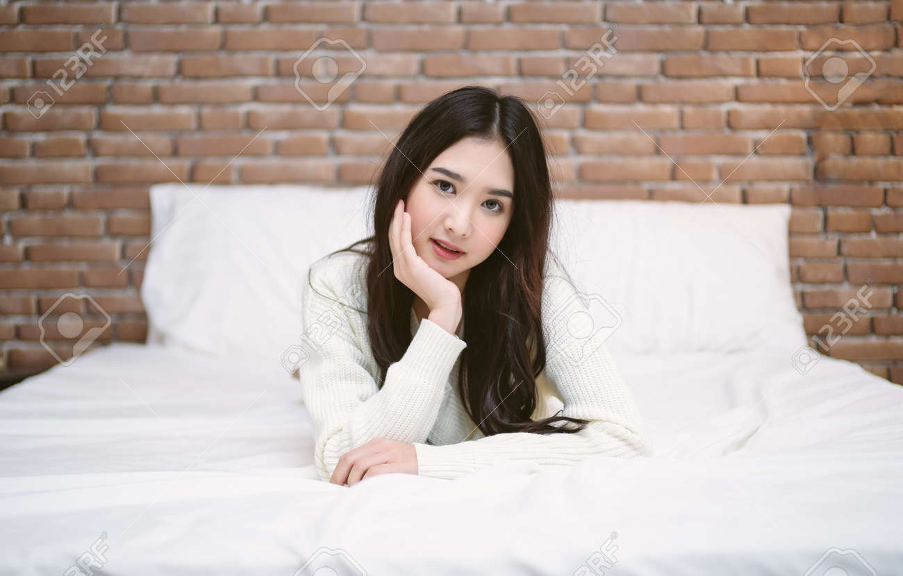Portrait of young Asian woman lying at the end of the bed underneath the quilt and looking at camera at home, bedroom in loft style. Enjoys morning weekend concept. - 173415227