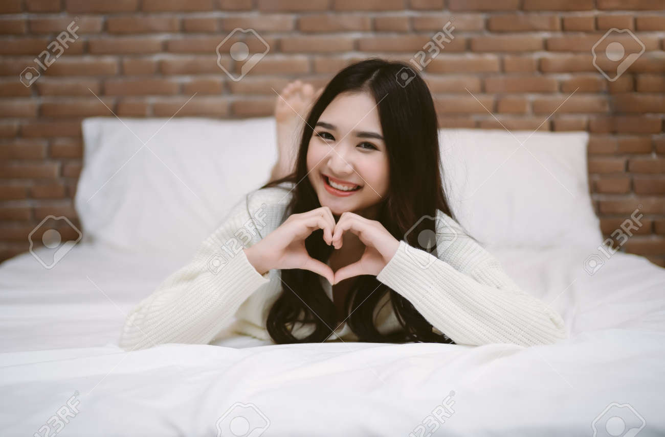 Happy young Korean girl lying at the end of the bed shows gesture heart with fingers and looking at camera. Portrait of smiling lady posing in bright home apartments. Concept happiness and love. - 173415230