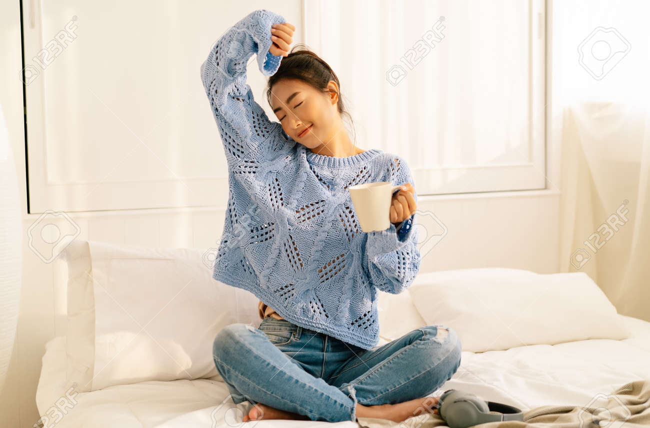 Portrait of smiling young Asian woman wearing knitted warm sweater and holding cup of coffee or tea while relaxing sitting on bed in the morning at home, Lazy day off concept. - 172843912