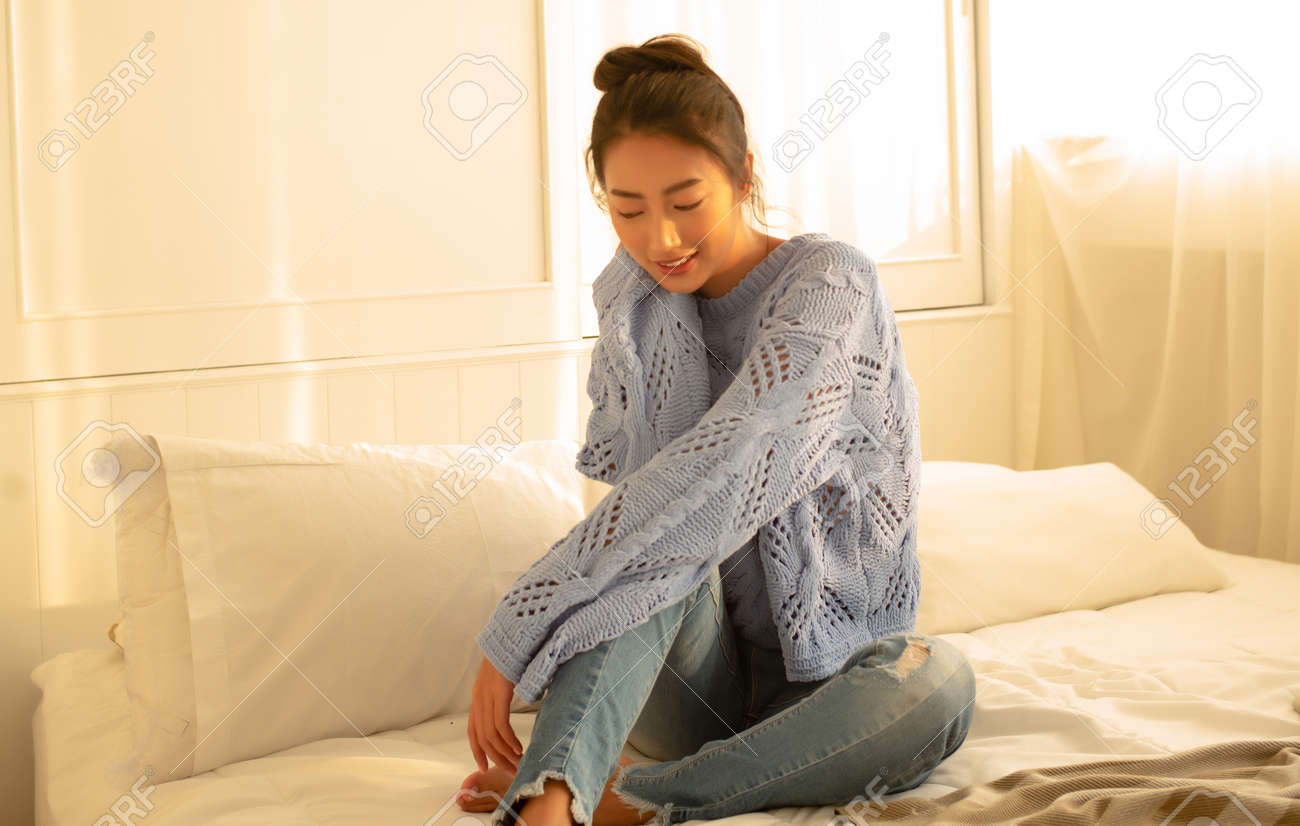 Portrait of beautiful young woman smiling friendly in knitted sweater enjoying sunny evening while sitting on bed in bedroom. Concept woman lifestyle and winter. Autumn, Winter atmosphere. - 173415231