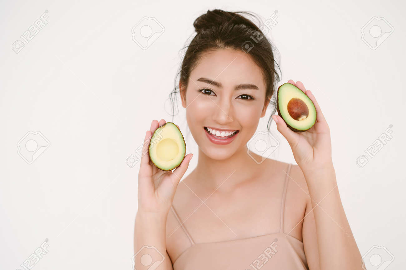 Beautiful young Asian woman with healthy glow perfect smooth skin and holding avocado in hands near the face isolated on white background. Skin care, beauty Natural, Healthy Lifestyle, Health Concept. - 173415233