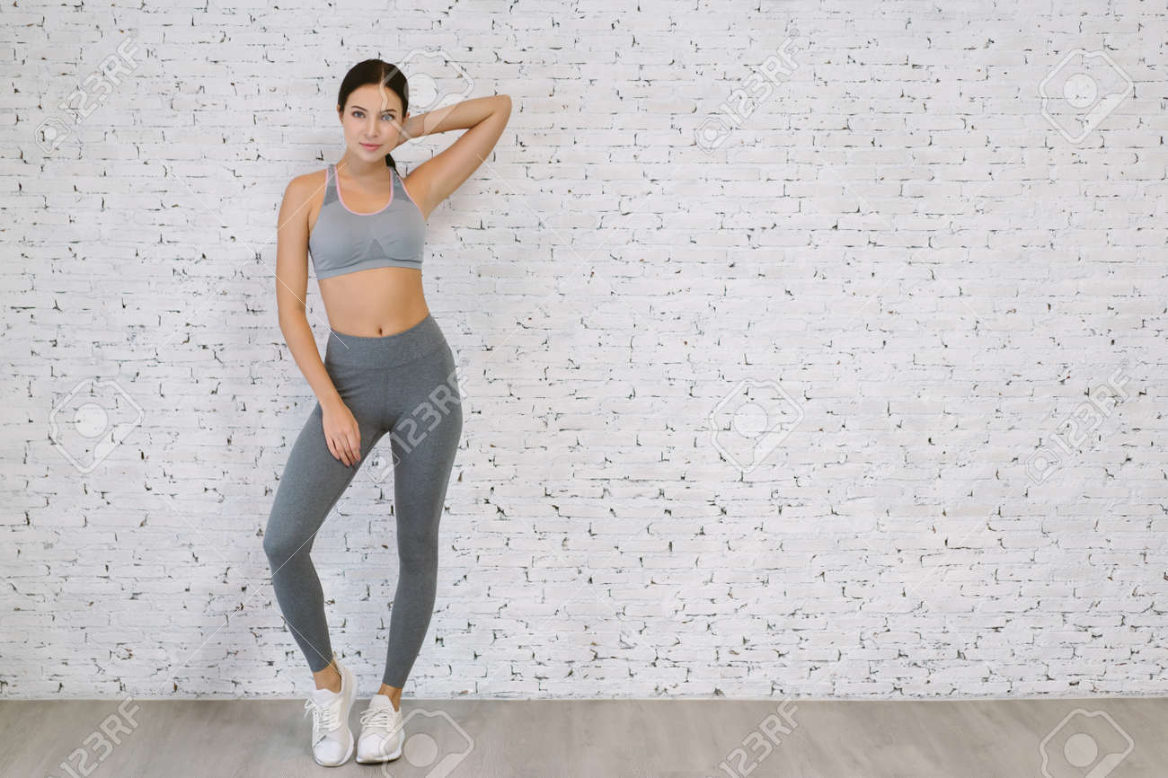 Portrait of beautiful smiling happy young woman wearing gray sportswear standing pose, looking at camera at white brick wall, exercise indoor full length, loft studio, copy space. Healthy life concept - 173783992