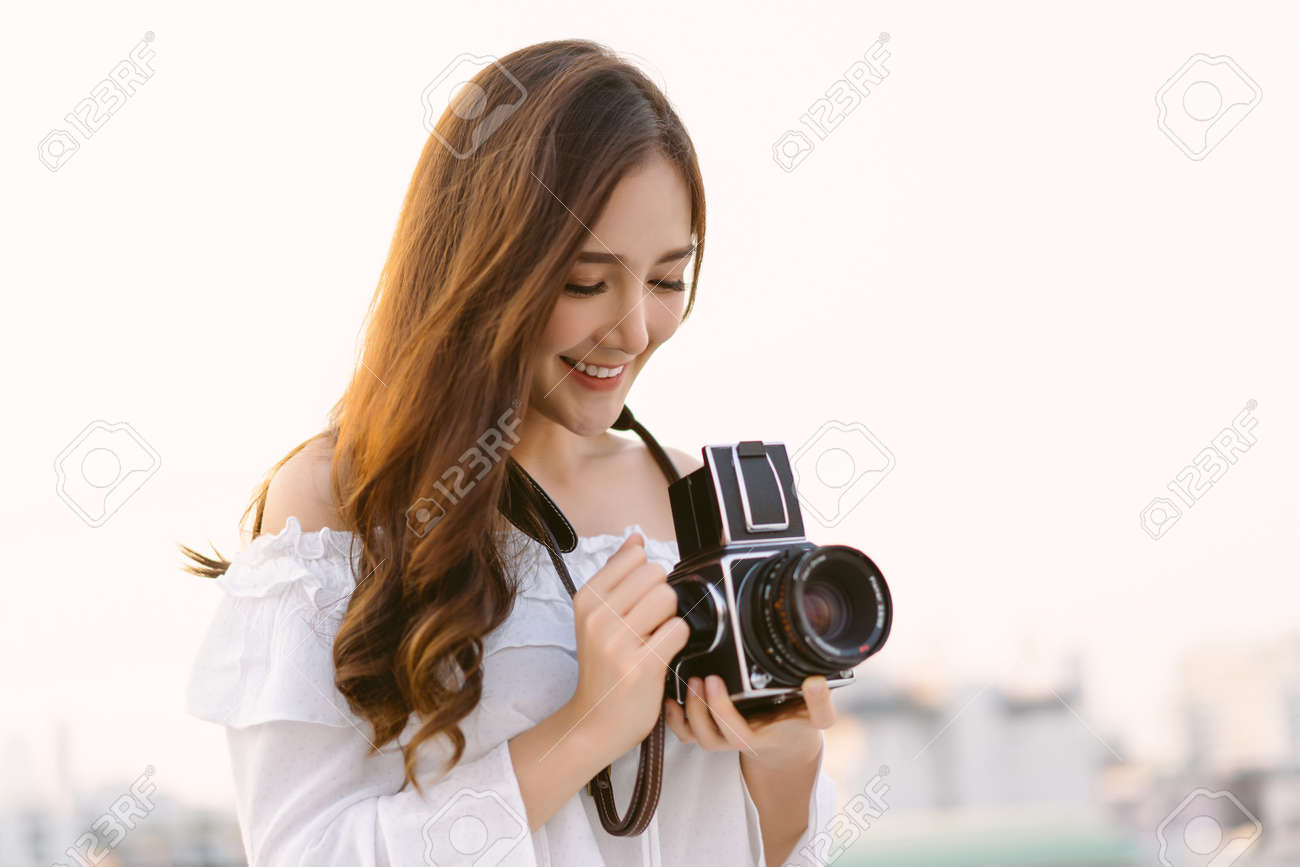 Beautiful young Asian stylish woman taking photos with retro film camera on the rooftop of a building. Asian girl smiling enjoy weekends, Holiday lifestyle trip. - 173785669