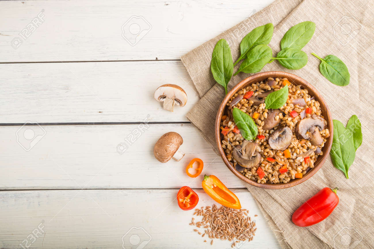 Spelt (dinkel wheat) porridge with vegetables and mushrooms in wooden bowl on a white wooden background and linen textile. Top view, flat lay, copy space. Russian traditional cuisine. - 157950294