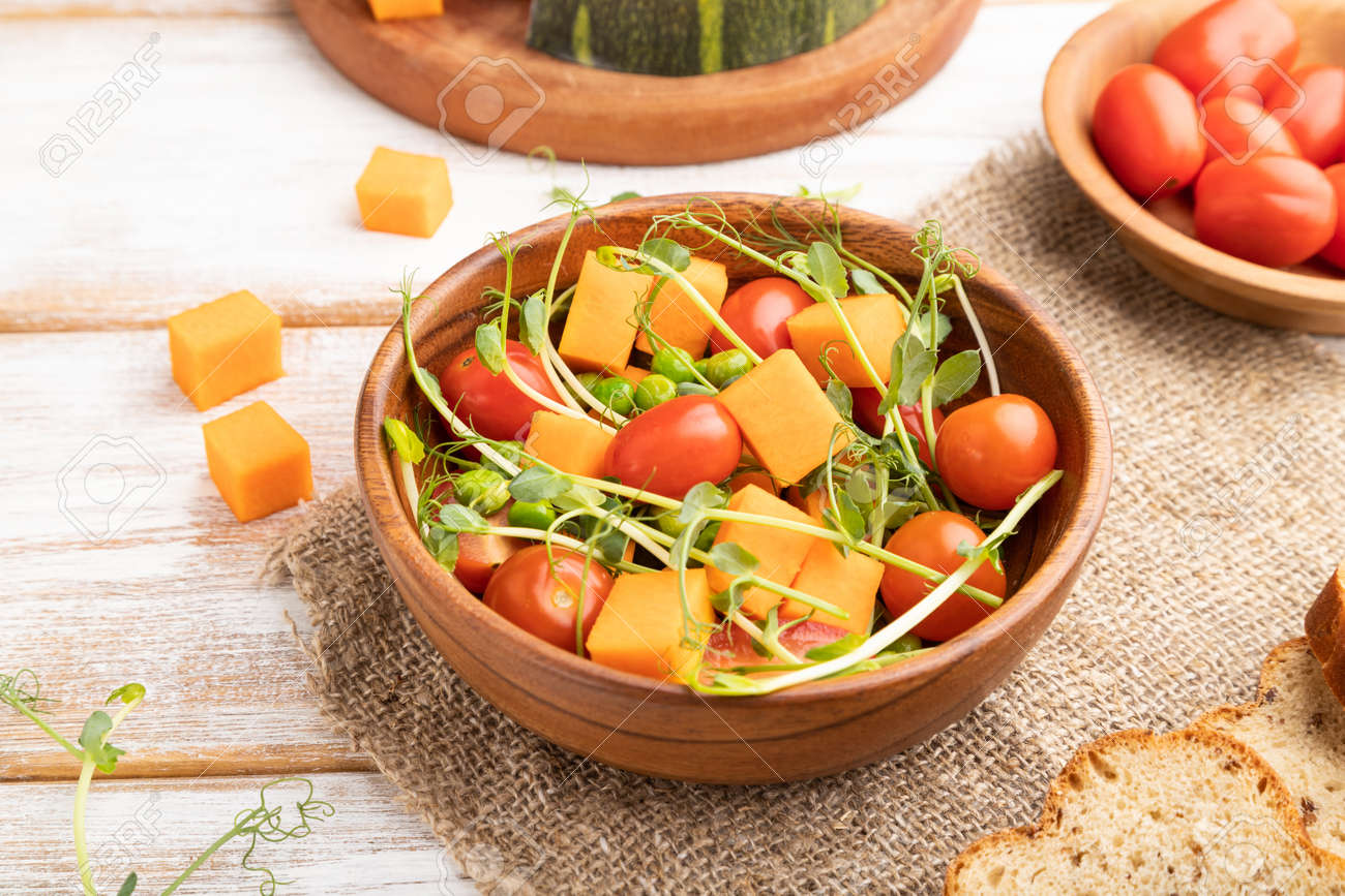 Vegetarian vegetable salad of tomatoes, pumpkin, microgreen pea sprouts on white wooden background and linen textile. Side view, close up. - 169839460
