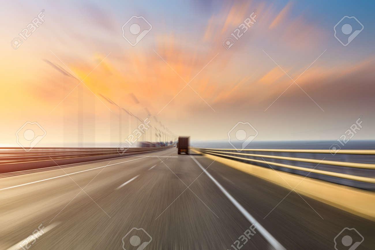 Blurred motion of truck and asphalt road at dusk - 136787991