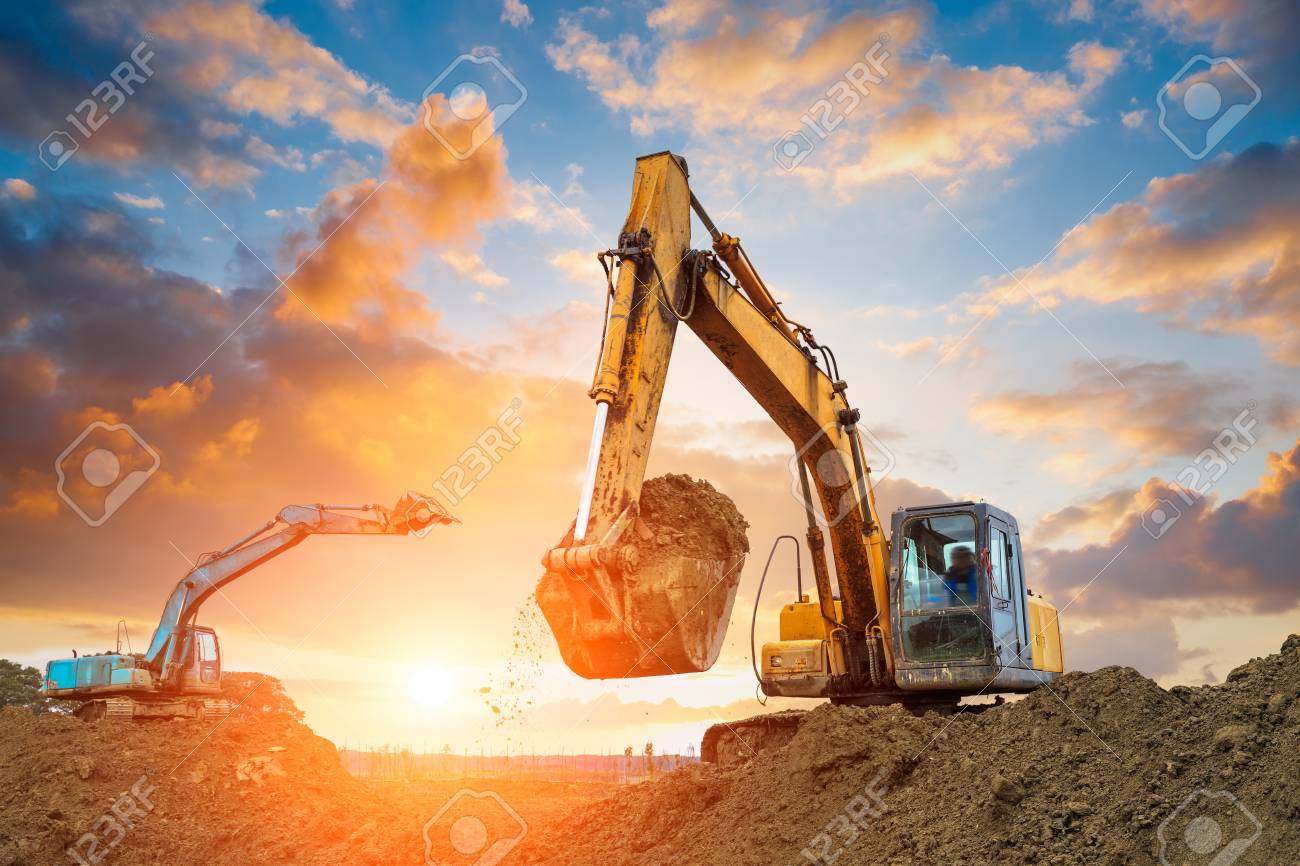 excavator in construction site on sunset sky background - 76009550