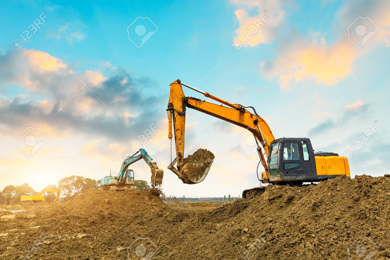 excavator in construction site on sunset sky background - 76009553