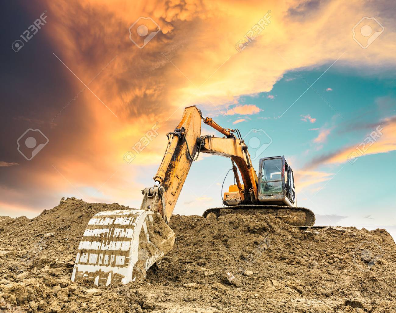 Excavator working at construction site on sunset - 89252891