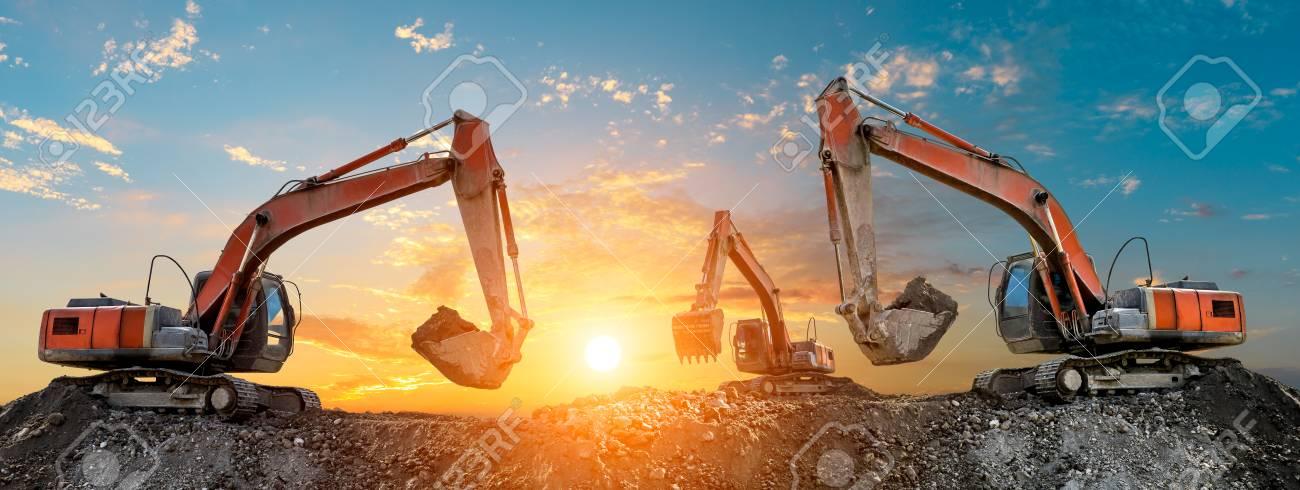 Three excavators work on construction site at sunset,panoramic view - 113297406