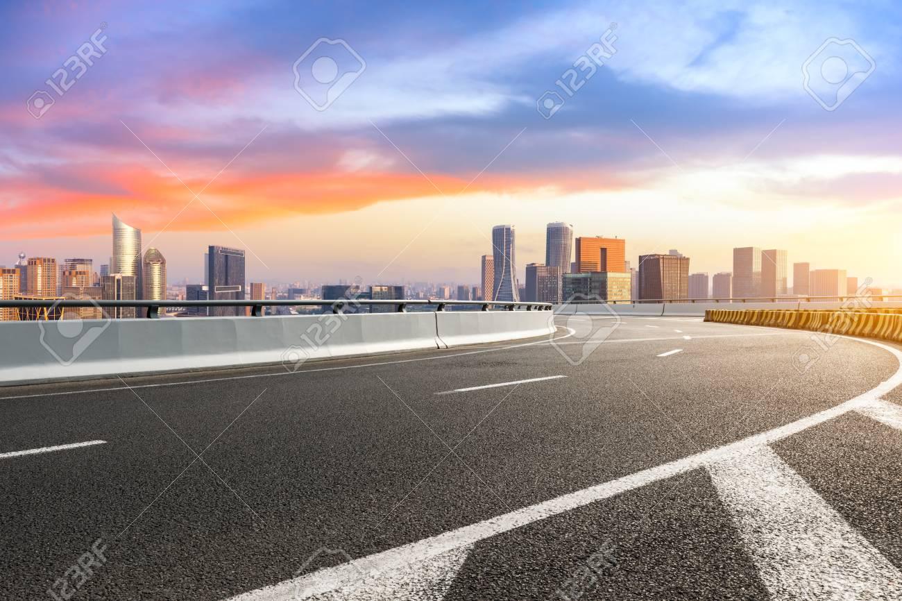 Empty asphalt road and city skyline at sunrise in hangzhou - 115306378