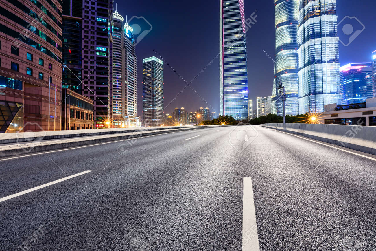 Shanghai modern commercial office buildings and empty asphalt highway at night - 122031320