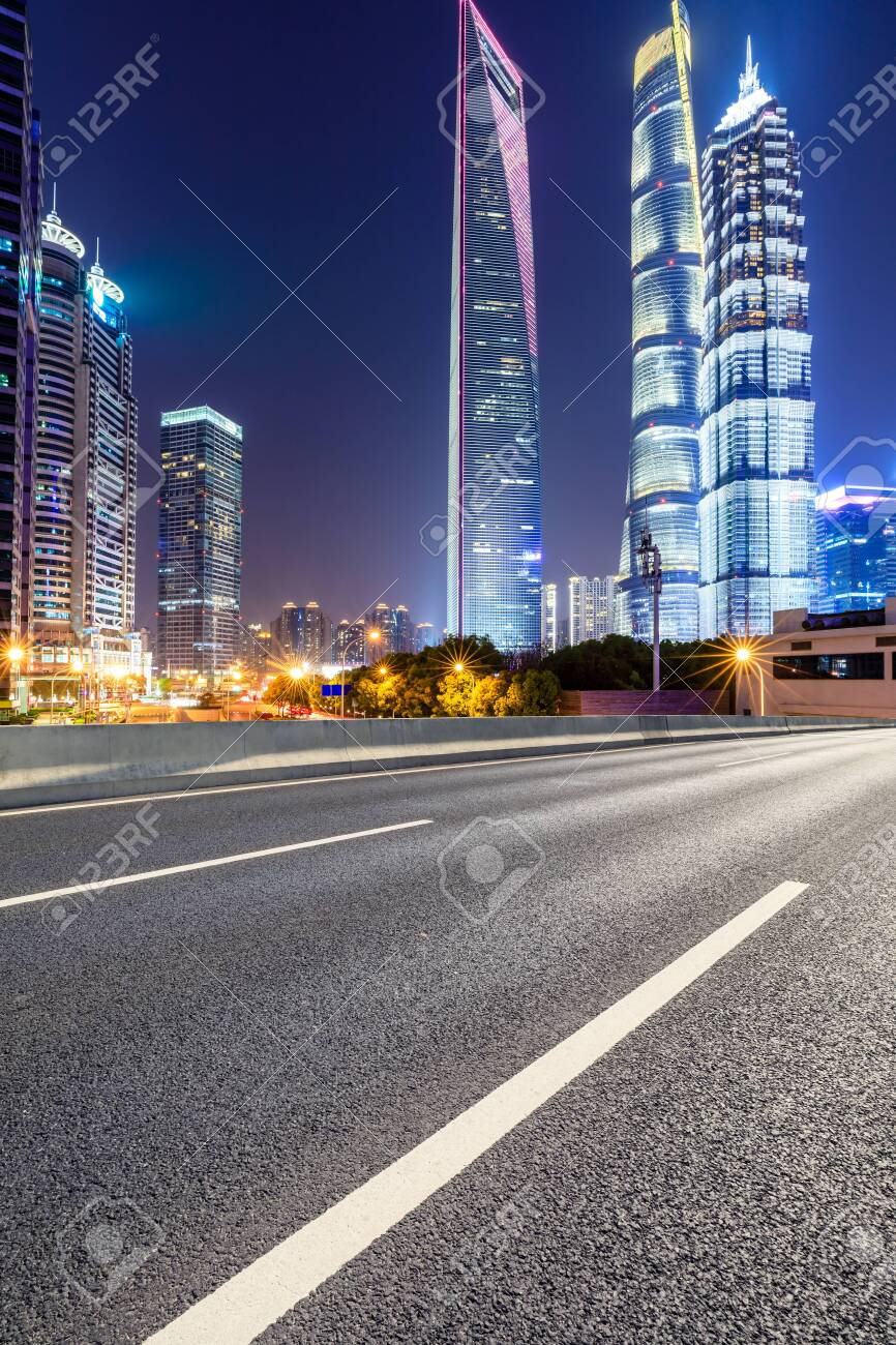 Shanghai modern commercial office buildings and empty asphalt highway at night - 122031376