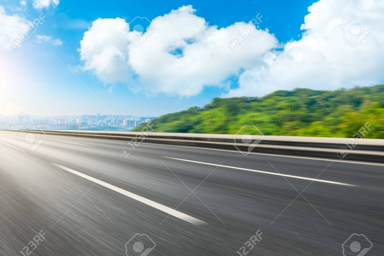 Motion blurred asphalt road and green mountain with city skyline in Hangzhou. - 148971972