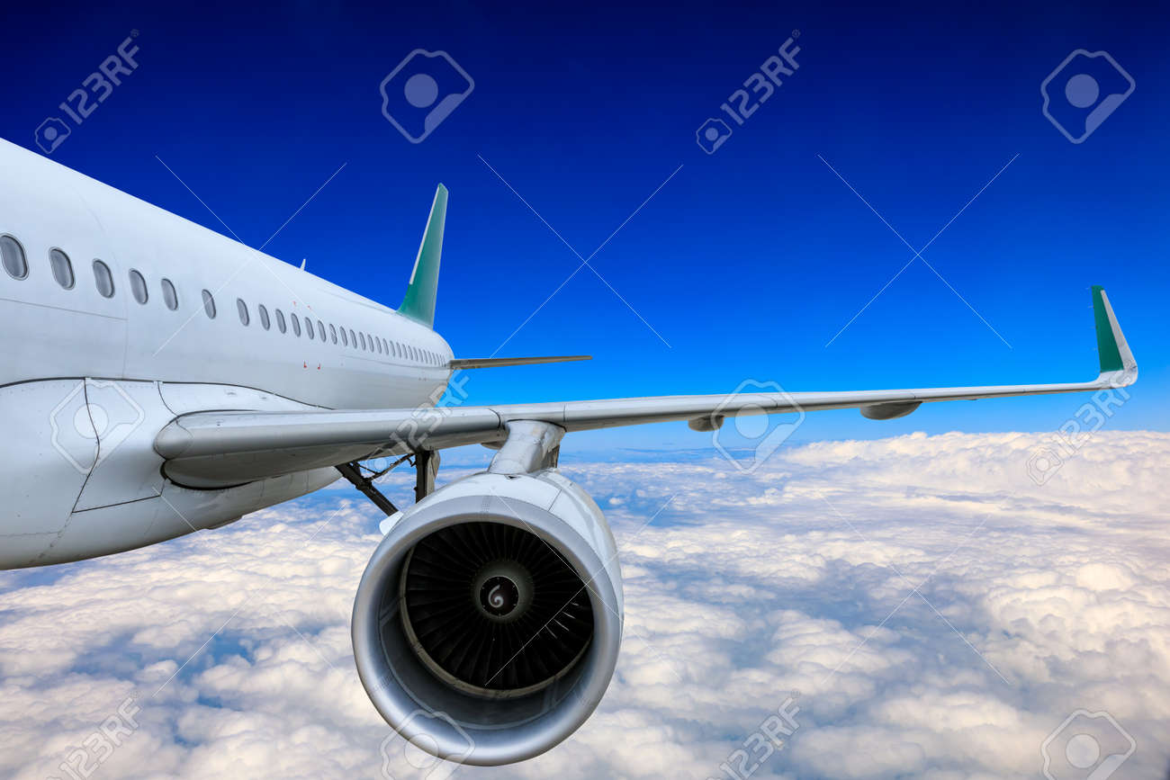 Commercial airplane flying above blue sky and white clouds. - 158669128