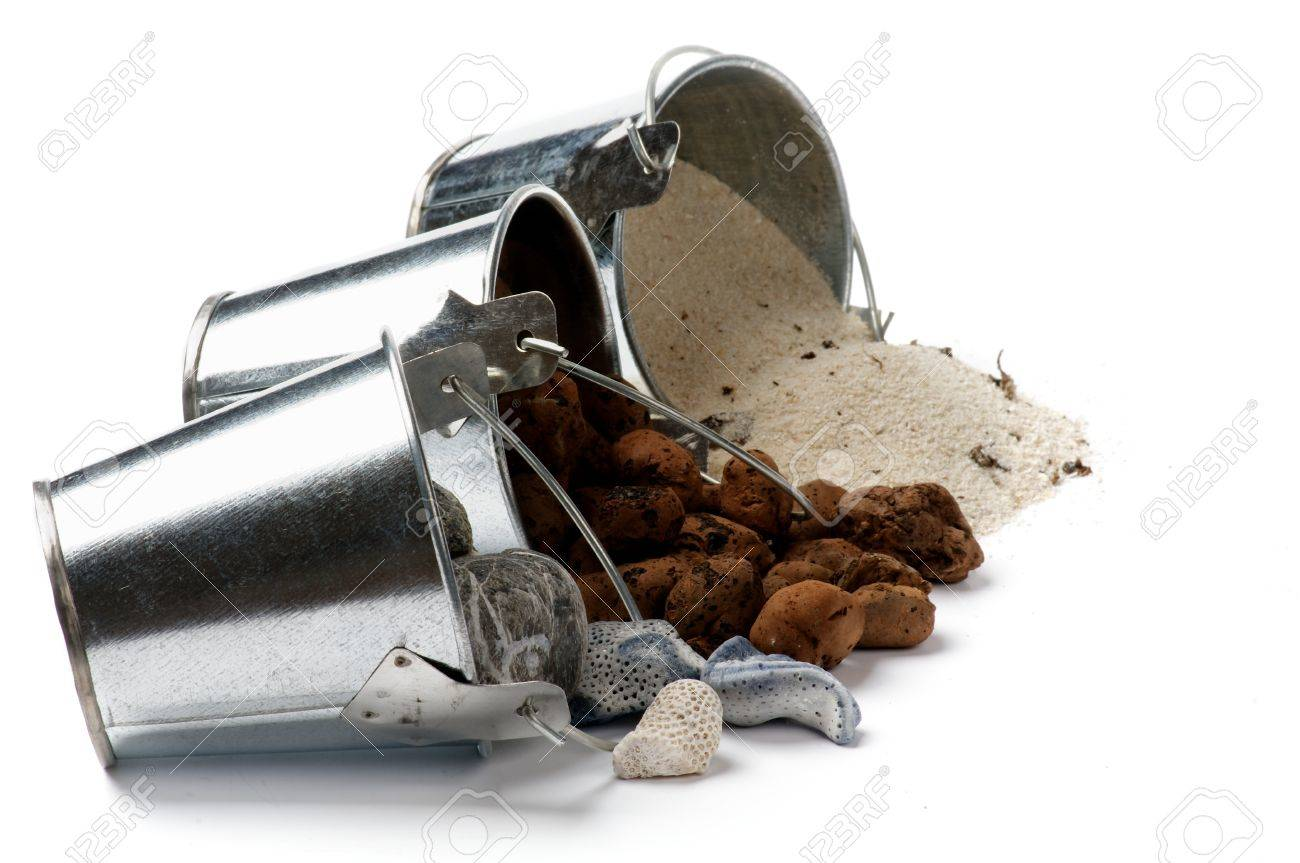 tin buckets with spilled gravel sand and stones in a row isolated on white background