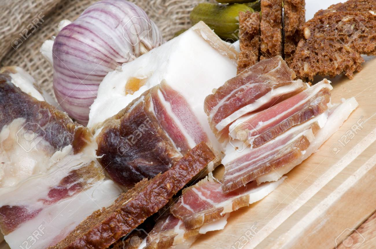 Raw Smoked Homemade Bacon Full Body and Slices with Garlic, Brown Bread and Gherkins closeup on Cutting Board Stock Photo - 17126978