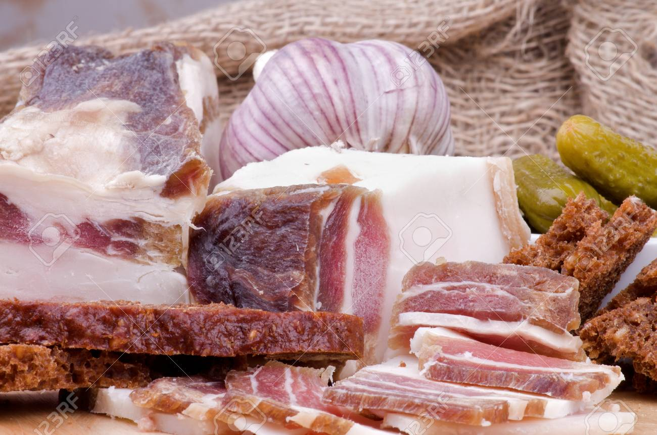 Arrangement of Raw Smoked Homemade Bacon with Brown Bread, Garlic and and Marinated Gherkins closeup on Sacking background Stock Photo - 17358963