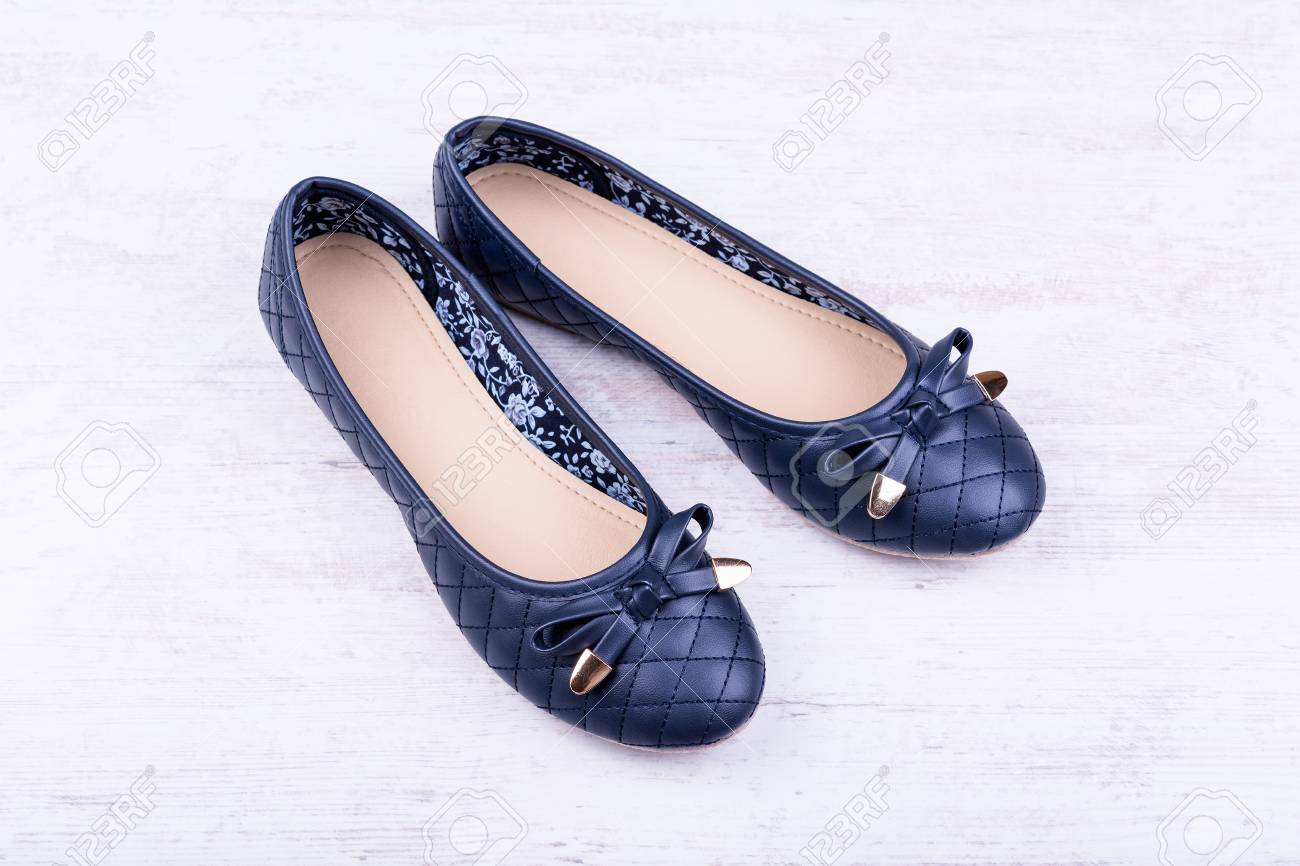 bf61c06b2 Pair of dark blue ladies' flat shoes on white wooden background. Stock  Photo -