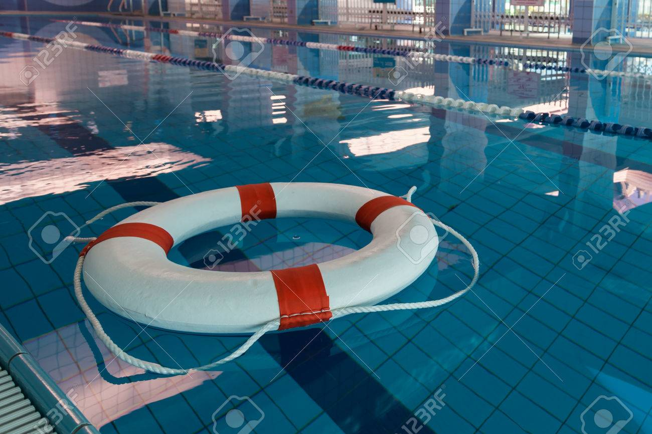 A red and white lifebuoy (Kisby Ring) floating in a covered swimming..