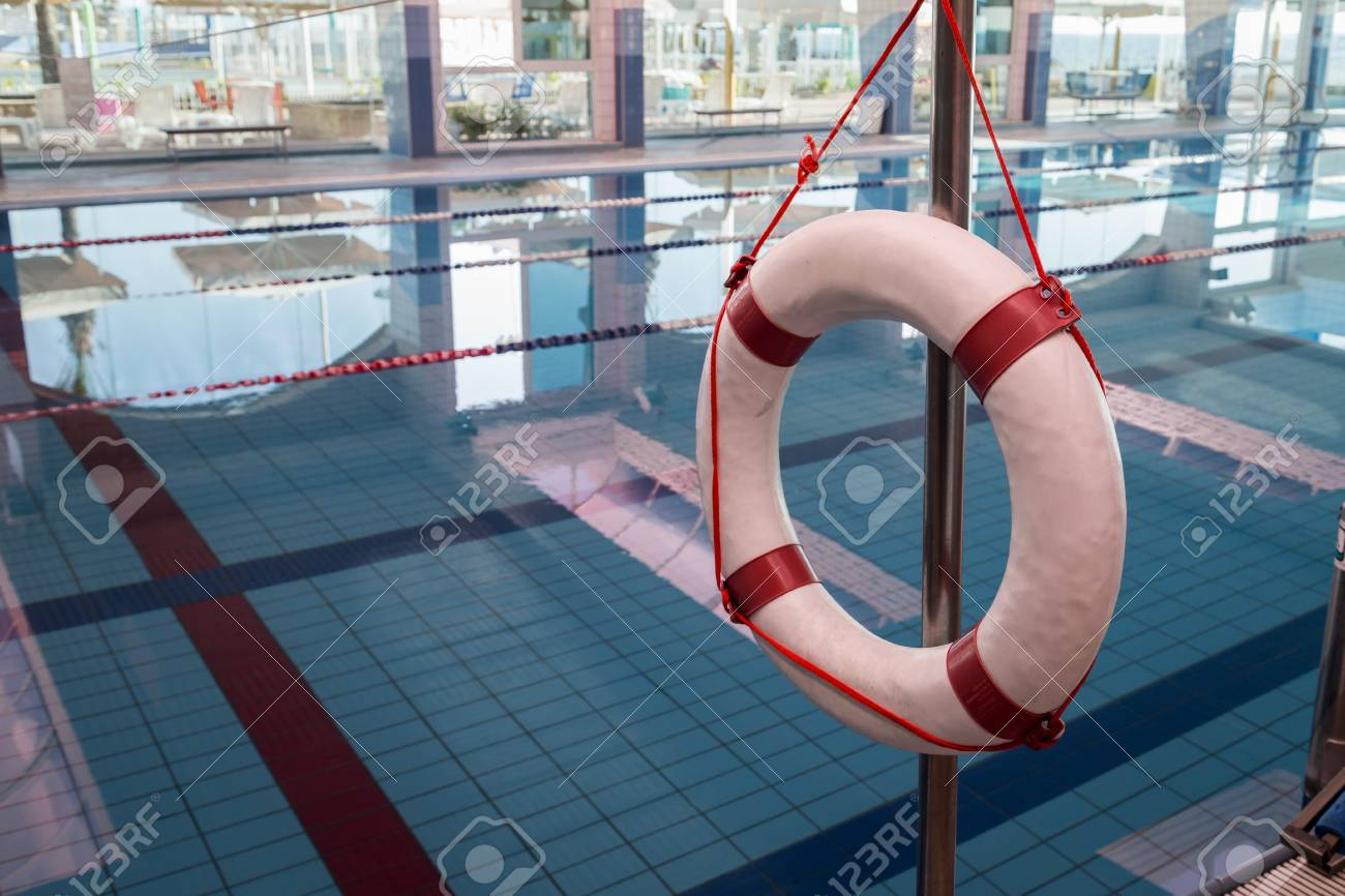 A red and white lifebuoy (Kisby Ring) hanging near a covered..