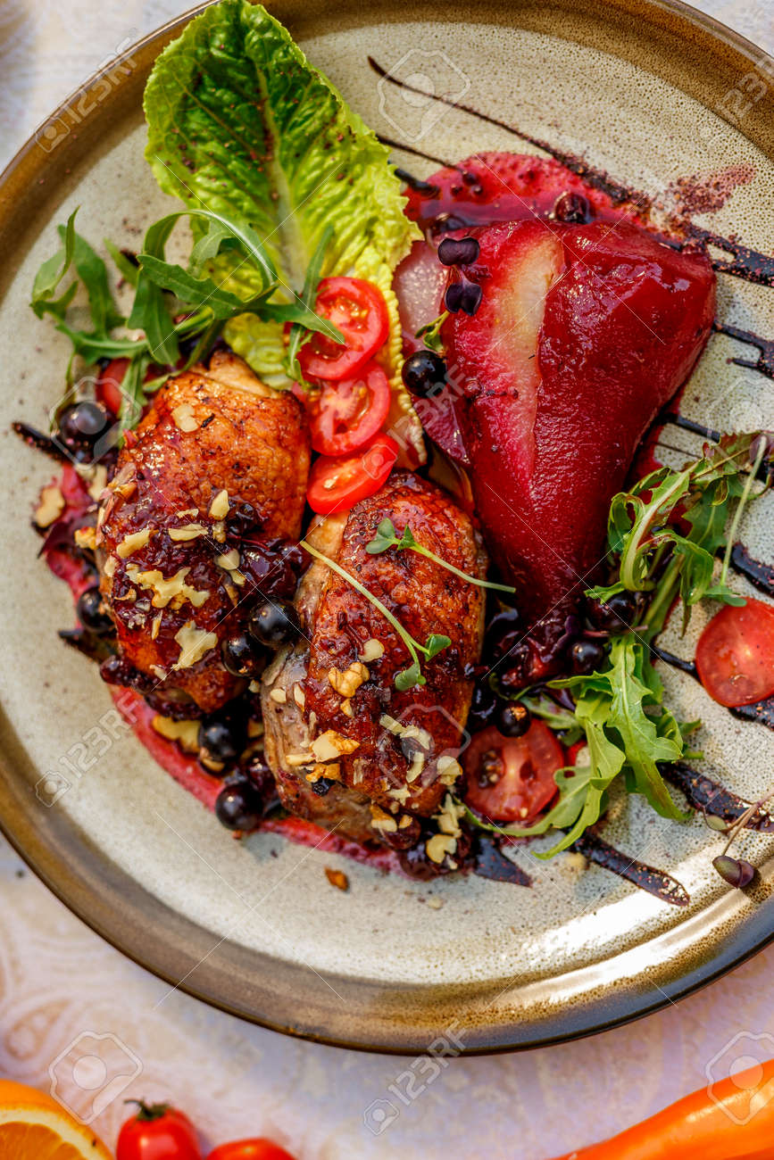 chicken thighs with rucola, nuts and vegetables on a decorated table - 145896888