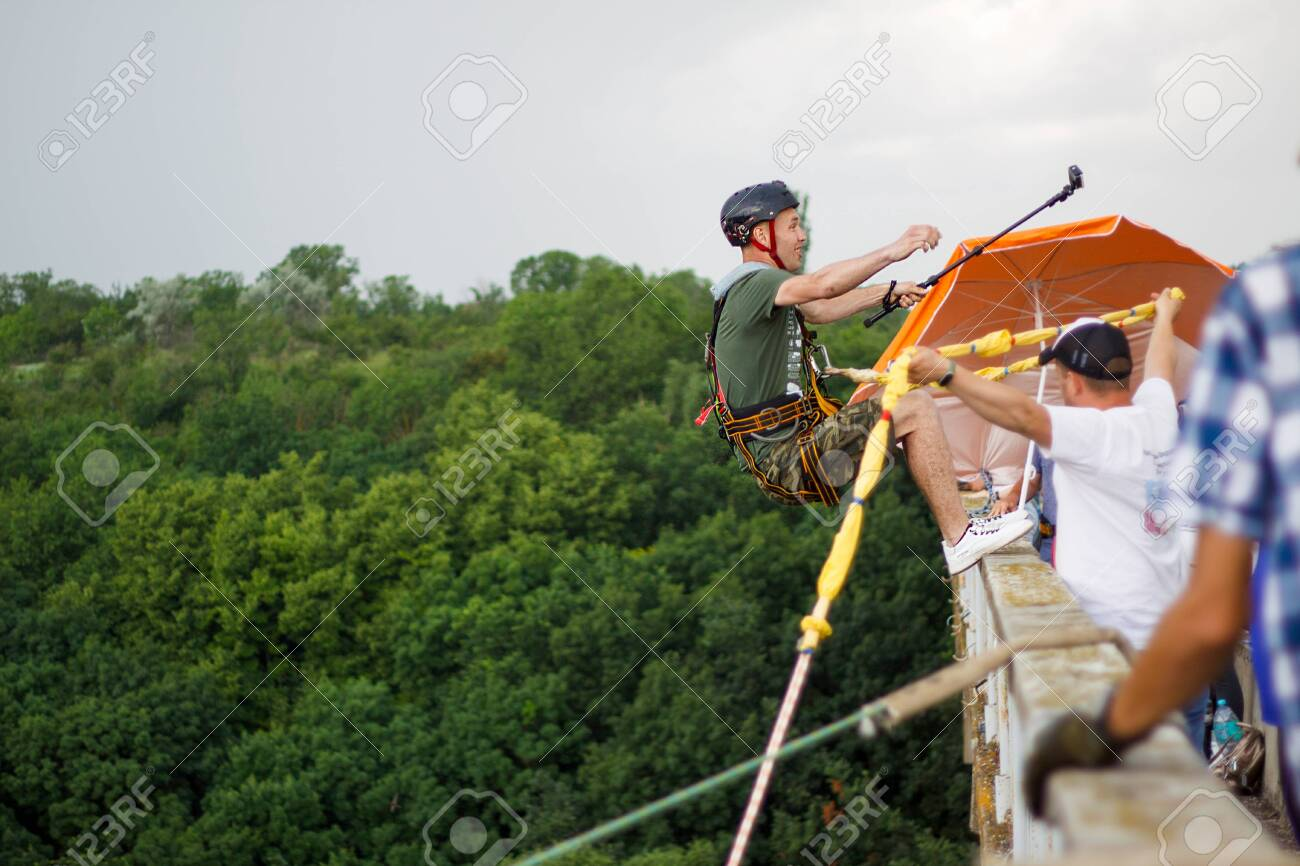 Concept of Extreme Sports and Fun. A man is a thrill-seeker and a rope jumper from the bridge. He is very happy to make a dream come true. He is holding an action camera and insanely happy - 150805823