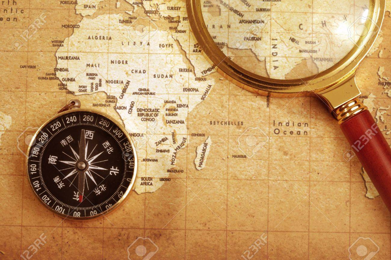 An old brass compass on a Treasure map background ,with Magnifier Stock Photo - 13537729