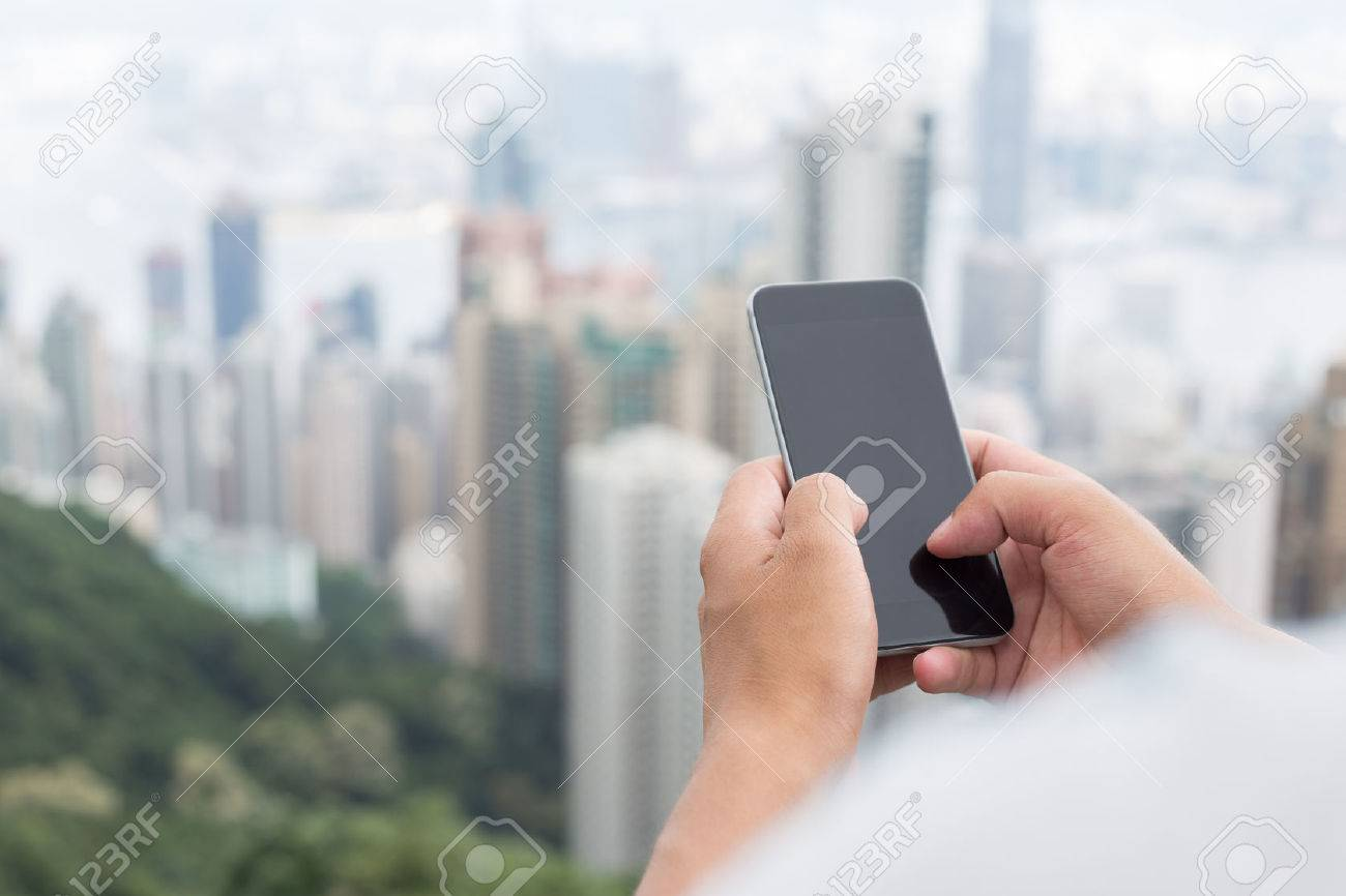 hand holding mobile phone with cityscape as background - 42370559