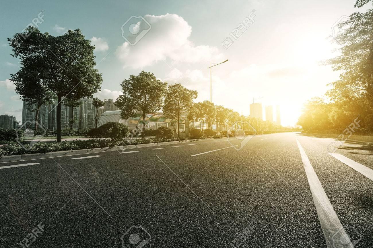 empty asphalt road with trees under sunshine - 45528152