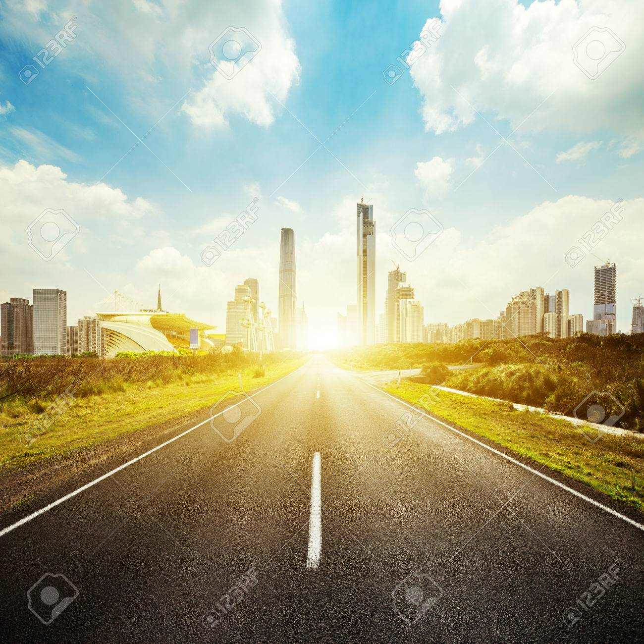 empty asphalt road with greenland aside and skyscrapers under sunbeam - 45548639
