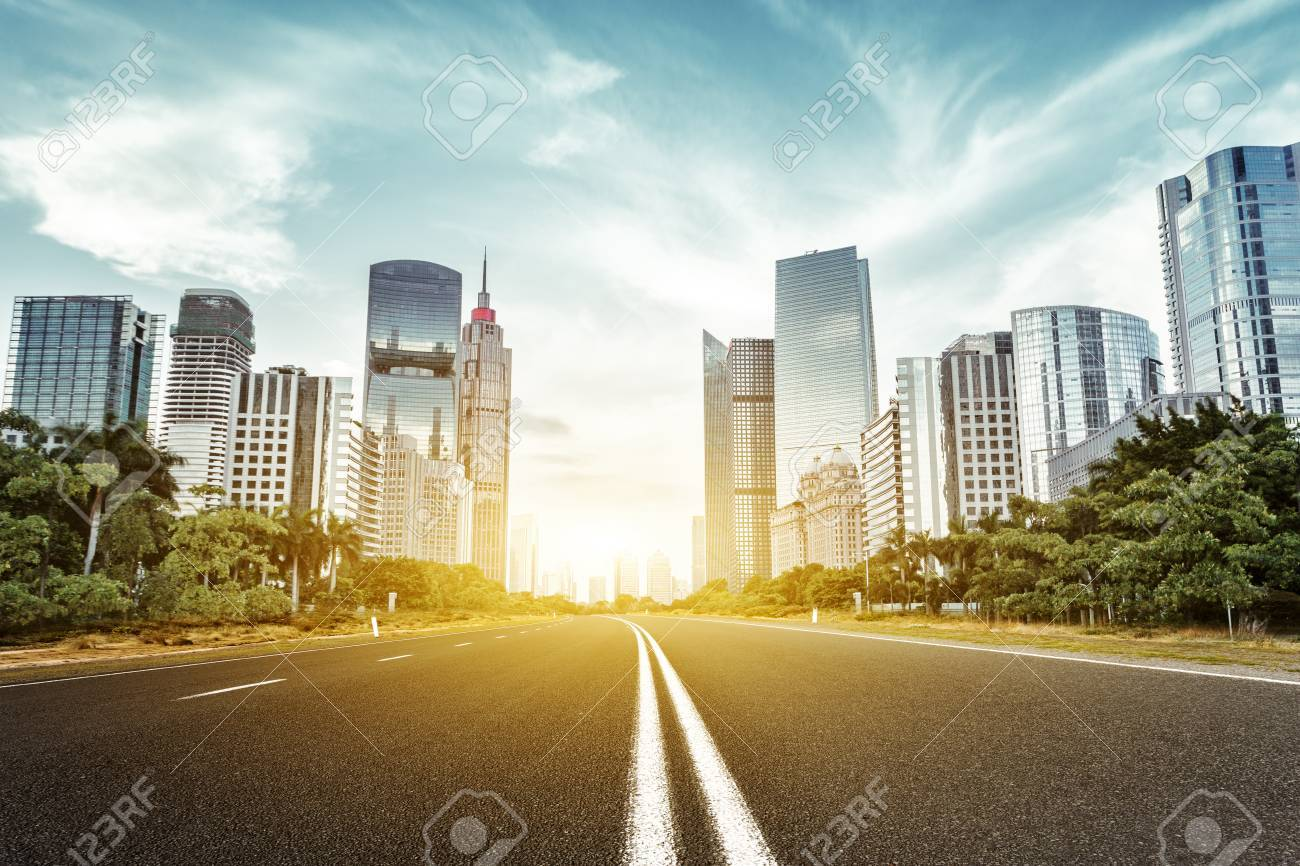 empty asphalt road with trees aside and skyscrapers under sunbeam - 45529708