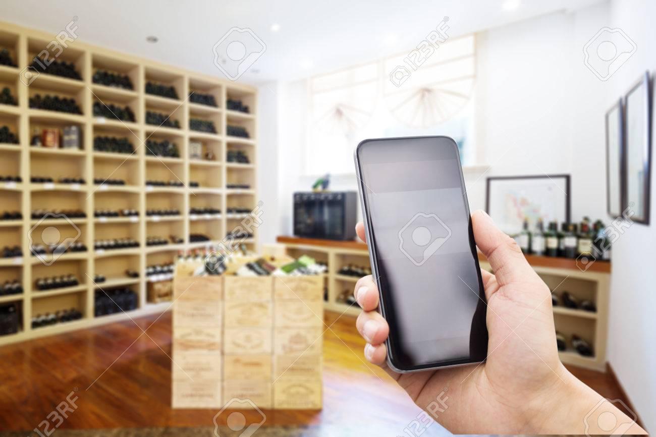Téléphone mobile avec écran vierge dans la cave à vin moderne