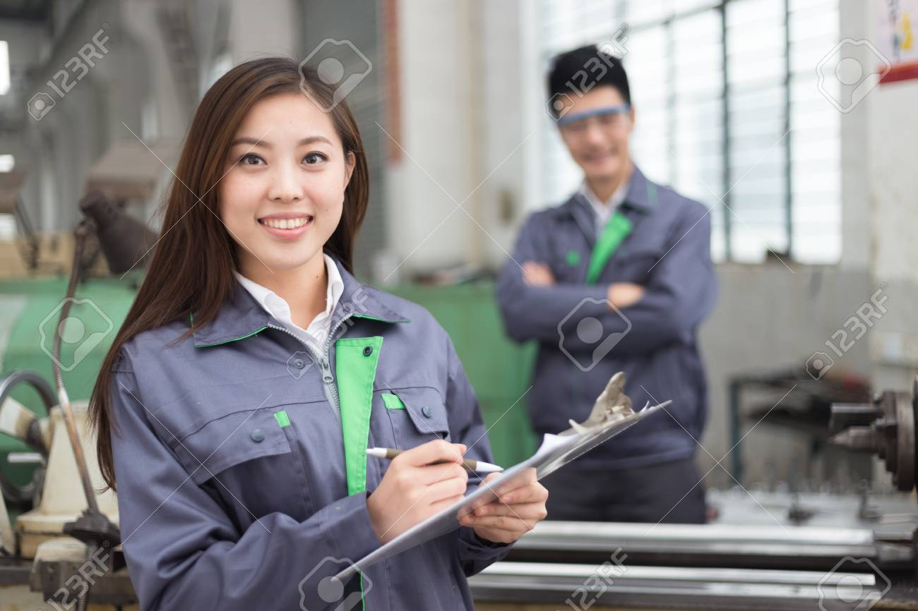 young chinese man and woman work in motor manufacturing factory - 93518747