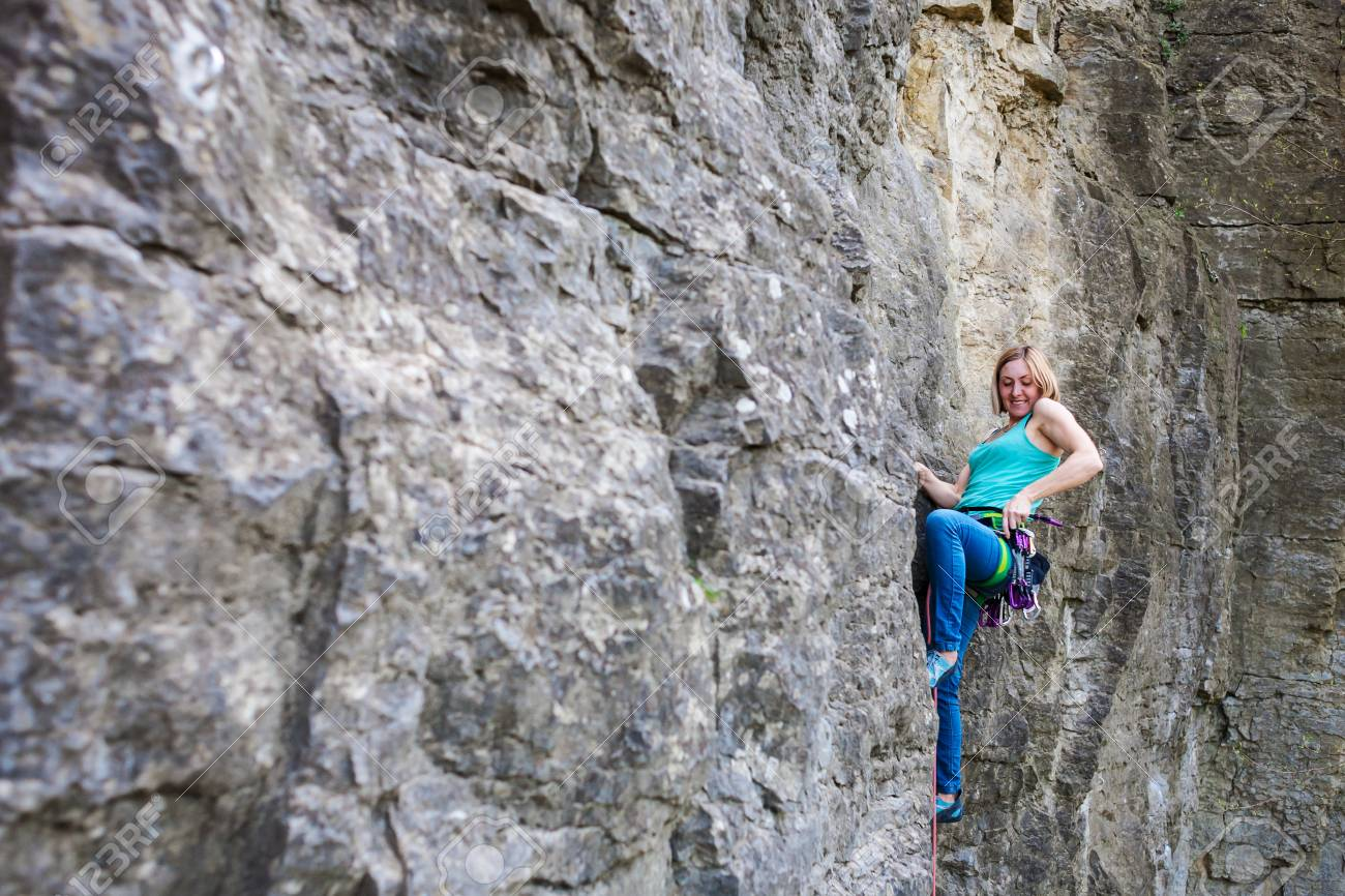 A rock climber on a rock  A woman goes in for sports in nature
